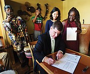 Mayor Martin Walsh signs the Acoustic Live Entertainment Ordinance during a celebration at Roxbury's Suya Joint. City Councilor Michelle Wu sponsored the bill.