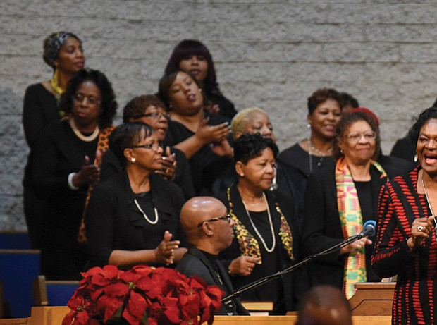 The Rev. Delores McQuinn, right, a member of the Virginia House of Delegates, sings with the choir during the service.