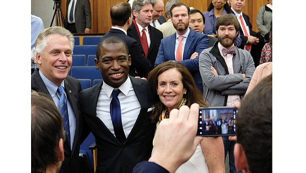 Newly installed Richmond Mayor Levar Stoney smiles for a photo with his friend and mentor, Gov. Terry McAuliffe, and First Lady Dorothy McAuliffe after last Saturday's swearing-in ceremony at City Hall.
