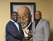 "Author Calvin Quarles gives Rev. Dr. David G. Latimore a copy of his new book ""The Panther at the Cross"" at Mount Zion Baptist Church in Joliet in front of a painting of the former elected pastor Rev. Dr. Issac Singleton."