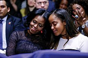 First Lady Michelle Obama and daughter Malia embrace as President Obama warmly acknowledges them during his speech.