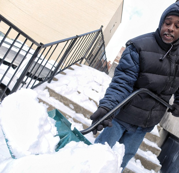 Kelvin White clears away snow at 5th and Franklin streets in Downtown, just one of the legions who shoveled steps, sidewalks and parking places across the area.