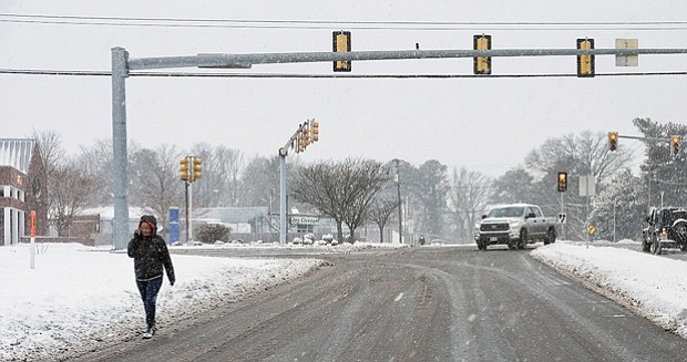 Intrepid pedestrians and motorists are quickly out and about after the snow stops falling Saturday. Location: Parham Road and Broad Street in Western Henrico.