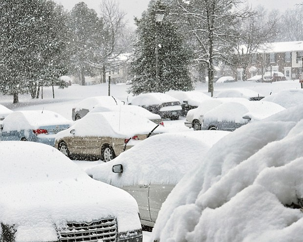 Parked cars at Muldoon Court and Shrader Road are blanketed with snow Saturday.