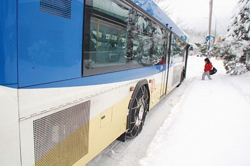 A passenger wades through a foot of snow to catch a TriMet bus on Northeast Martin Luther King Jr. Boulevard at the beginning of a week of snow and ice covered roads and walkways. A big melt was starting Tuesday with freezing rain and then just rain as more mild conditions move in for the rest of the week.
