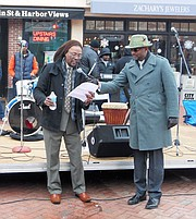 Terrell Freeman, left, leads a libation ceremony. Darius A. Stanton, right, serves as the new Chair of the Annapolis Martin Luther King, Jr. Parade Committee. Stanton wants to continue bringing the community together in peace, love, and un