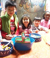 Casey and Lilyrose Emeogo join Zoey and Kyle Zylestra, and Ethan and Gavin Wang in creating birthday cards for Dr. Martin Luther King at Port Discovery's MLK celebration.