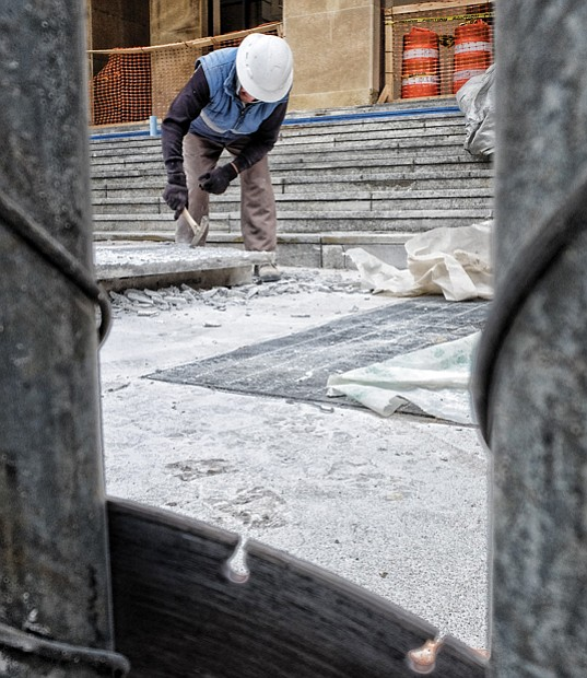 A worker from Stonee Masonry of Henrico County crafts new steps for the Main Library in Downtown. The facelift was needed because the old steps were cracked and broken. The nearly $100,000 project is almost complete, despite delays from recent snow and rain.