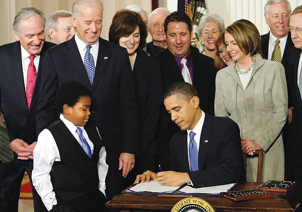 Surrounded by members of the U.S. House of Representatives and Senate, President Obama signs the Affordable Care Act in March 2010 as youngster Marcelas Owens of Seattle watches.