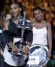 United States' Serena Williams, left, holds her trophy after defeating her sister, Venus, right, in the women's singles final at the Australian Open tennis championships in Melbourne, Australia, Saturday, Jan. 28, 2017. (AP