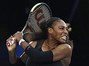 United States' Serena Williams follows through on a backhand return to her sister Venus during