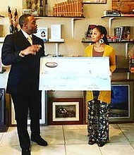 Freedom Ties Co-Founder Tavares Bethel presents a check to Maeva Jackson, founder of Black