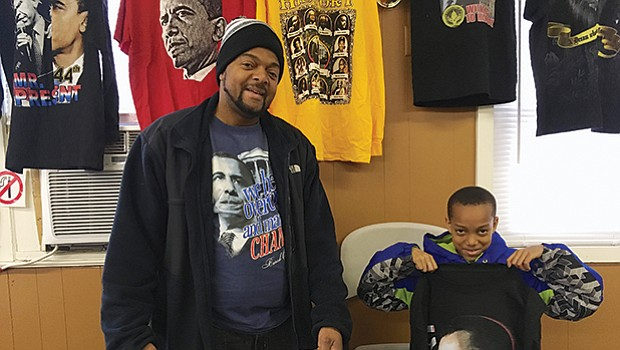 Danny Steele and his son DJ with Obama-themed products for sale by D. Steele Enterprise at Ujamaa Bazaar.