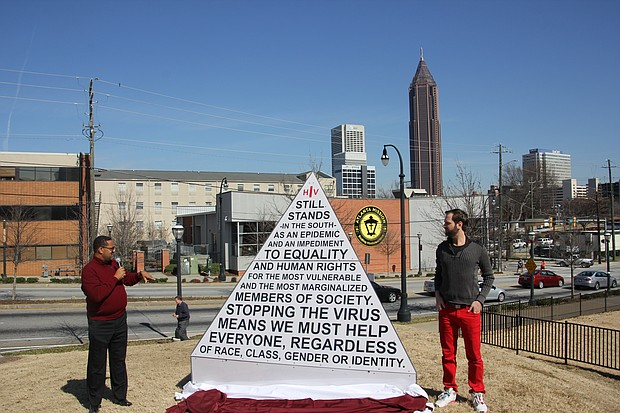 Imara Canady, left, helped unveil the HIV clock that Matthew Terrell, right, created to count the number of greater Atlanta residences living with the disease. He will keep tabs every Friday until June 27, National HIV Testing Day.
