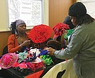 Juanda Alexander (r) of Juanda's Hattitude sets up her hat display at Ujamaa Bazaar, with help from her daughter Shonna Alexander.