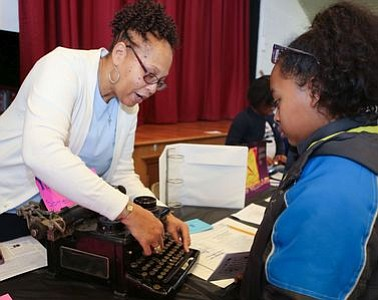 "Member of Zeta Phi Beta Sorority, Inc.,  with attendee Ashley Ward at the ""Typewriting Machine"" - Lee Burridge and Newman Marshall station. -- Photo by April A. Ward"