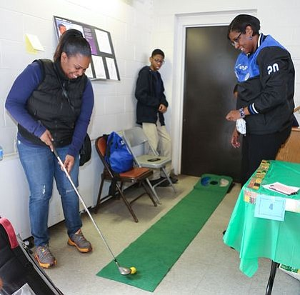 "Member of Zeta Phi Beta Sorority, Inc.,  with attendee playing a hole in one at the ""Golf Tee"" - Dr. George Grant and David M. Bondu, Sr. station. -- Photo by April A. Ward"