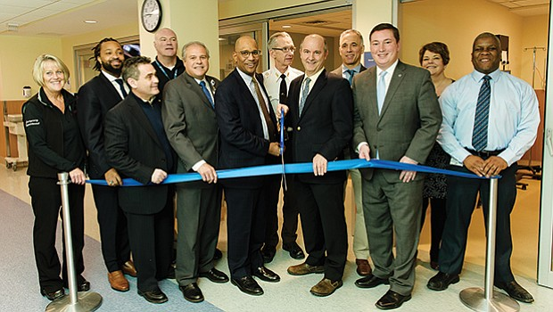 Carney Hospital President Walter Ramos cuts the ribbon on the newly renovated and expanded Emergency Department with local elected officials and community leaders.