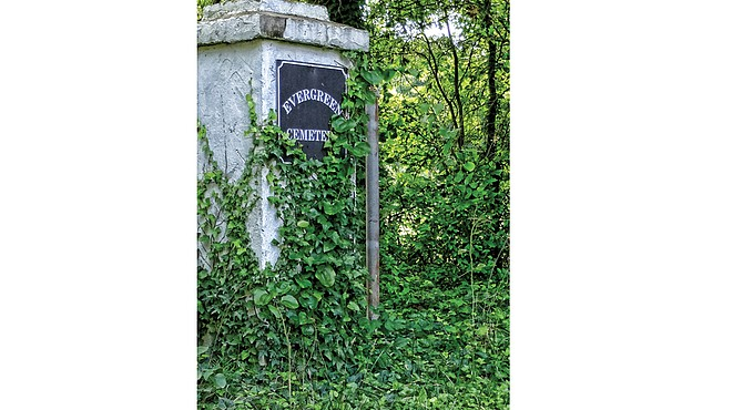 Vines cover the entry pillar to Evergreen Cemetery in this June 28, 2016, photo. The scene exemplifies the condition of much of the 60-acre burial ground despite efforts of volunteers to control wild plants. State funding will help supporters better maintain the historic graveyard. Location: Stony Run Parkway in Richmond's East End.