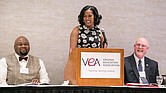 Jahana Hayes, center, the 2016 National Teacher of the Year, reacts to remarks during her talk last Friday at the Teachers of Color Summit in Downtown. Sharing the dais are, left, Dr. James J. Fedderman, vice president of the Virginia Education Association, and Jim Livingston, president of the statewide teachers group.