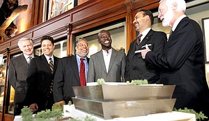 Team members from Freelon Adjaye Bond/SmithGroup, who designed the winning concept for the National Museum of African American History and Culture, meet with members of the Smithsonian Institution, from left, Hall David, Peter Cook, Director of the National Museum of African American History and Culture Lonnie Bunch, David Adjaye, Phil Freelon, and Smithsonian Secretary Wayne Clough. in front of a model of the winning design, in Washington, April 14, 2009.
