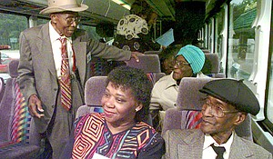 """Tuskegee Syphilis Study participant Fred Simmons, left, greets Dora Banks, right, after boarding a tour bus in Tuskegee, Alabama., May 15, 1997. The group was traveling to Washington, to accept an apology from the nation delivered by President Clinton for being denied treatment for Syphilis, the disease they knew as """"bad blood."""" At front center is Bernie Tolbert sitting with Carter Howard, another participant in the study."""