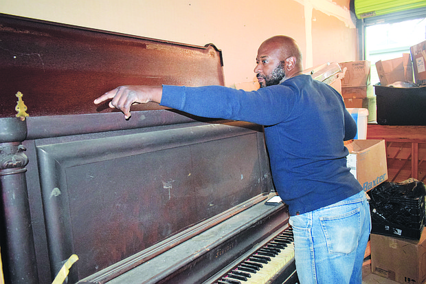 "After carefully opening the top of the Fischer piano in his possession, Dardanius L. ""DC"" Coleman notes the serial number, which he later checked and learned that the piano could very well have been around during W.C. Handy's time on Beale St. in the early 1900s."