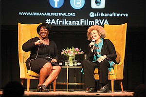 "Scholar and activist Angela Y. Davis, right, and Tressie McMillan Cottom, a Virginia Commonwealth University assistant professor, react to a member of the audience during Dr. Davis' appearance last Friday as the Afrikana Independent Film Festival's 2nd Annual ""Evening with an Icon."""