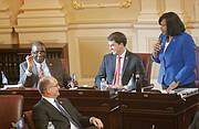"Petersburg Sen. Rosalyn R. Dance, right, introduces new Sen. Lionel Spruill Sr. of Chesapeake on the Senate floor.  Looking on are Sen. T. Montgomery ""Monty"" Mason of Williamsburg, front left, and Sen. Jeremy S. McPike of Woodbridge, center."