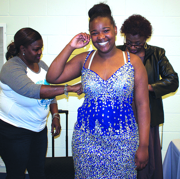 Volunteers were on hand to make minor alterations to prom dresses selected by Nieyia Buckhanon and other girls who attended Her Prom Closet.