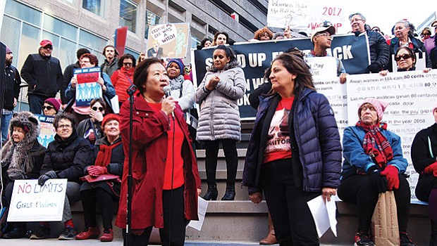 Suzanne Lee of the Chinese Progressive Association (left) and Roxana Rivera of 32BJ SEIU (right) kicked off a downtown rally during the International Women's Day last week.