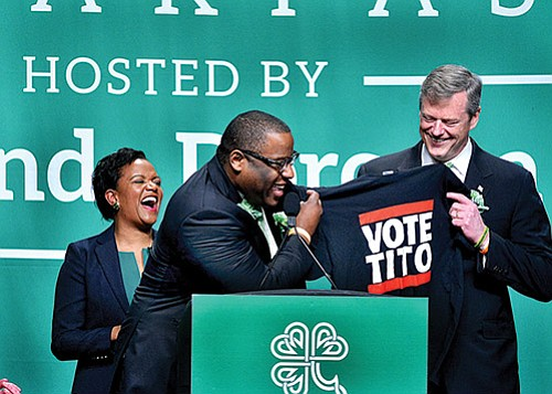 With typical satirical humor, mayoral candidate Tito Jackson (center) unveils a campaign t-shirt to the crowd at the annual St. Patrick's Day Breakfast as Gov. Charlie Baker and State Sen. Linda Dorcena Forry look on. This year marks the fourth consecutive year that the senator has hosted the event.