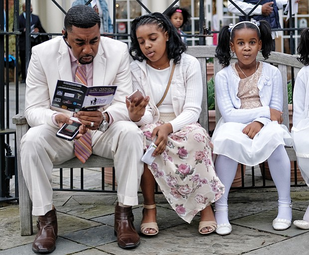 Freddie Royal takes a moment to peruse the activity schedule as he sits with his daughters, from left, Kyra, Amirah and Jada.