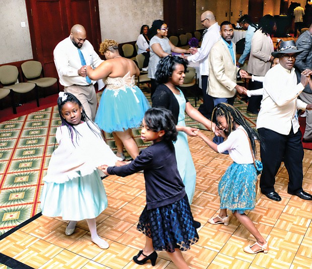 Father-daughter couples practice their salsa steps on the dance floor in the Massey Conference Center Auditorium at the garden's Kelly Education Center.