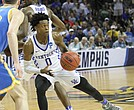 De'Aaron Fox of the Kentucky Wildcats shoots and scores on a trio of UCLA players.