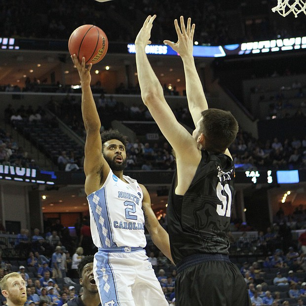 Joel Berry of North Carolina (left) shoot and scores over Nate Fowler of Butler.