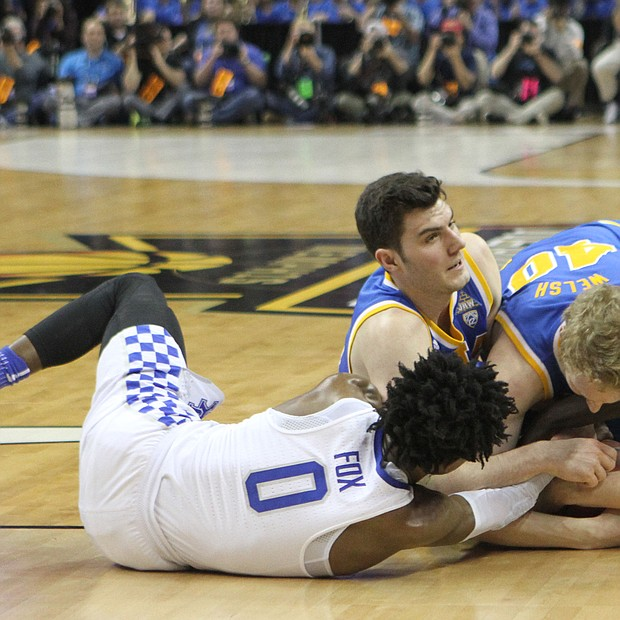 Kentucky and UCLA players battling for the loose ball.