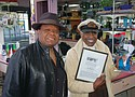 Bluesman Norman Sylvester presents business owner and entrepreneur Paul Knauls Sr. with a plaque to honor him for his nearly 30 years of support for the homegrown Inner City Blues Festival and the event's sponsorship of many community causes. The recent presentation was made at Knauls' Geneva's Hair Perfection Barber and Beauty Salon as ticket sales get underway.
