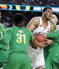 North Carolina's Kennedy Meeks drives between Dylan Ennis (31) and Dillon Brooks of Oregon Saturday in route to a 77-76 victory against the Ducks in the Final Four of the NCAA tournament.