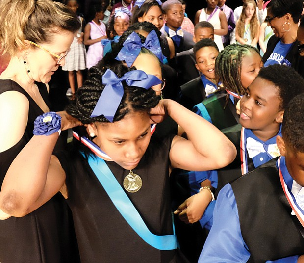 Masters of the dance // Fifth-grader Martierane Epps adjusts her medal, while Jahsai Fife admires his following Chimborazo Elementary School's Blue Team winning 1st place Monday in the Dancing Classrooms GRVA Colors of the Rainbow Team Match. Students from Broad Rock, J.L. Francis, Falling Creek and E.S.H. Greene elementary schools in Richmond and Chesterfield County competed in the merengue, foxtrot, rumba, tango and swing at the event held at Huguenot High School in South Richmond.