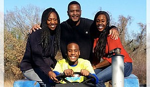 Jonita White poses with her husband and two children on an old tractor.