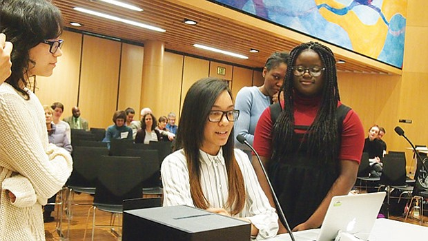 Surrounded by fellow members of the John W. McCormack debate team, Genesis Valdez speaks to the Boston School Committee about how the team garnered the best win-loss record in the Boston Debate League.