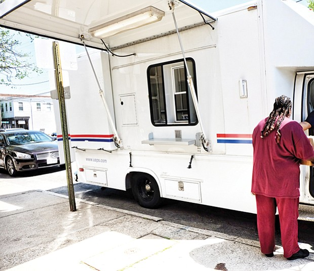 Post Office on Wheels // A customer takes care of business at the Post Office on Wheels that opened Monday outside the Church Hill Postal Station at 414 N. 25th St. The mobile center arrived after the building was shut down earlier that day to the dismay of residents.