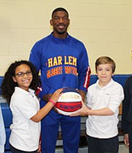 """Anthony """"Buckets"""" Blakes of the Harlem Globetrotters visited schools in Baltimore City and Baltimore County before the start of the team's 2017 World Tour. (Above) Students from St. Agnes Elementary School in Baltimore with Buckets Blakes (left to right) Finn Smith, Veronica King, Seamus Smith and Hahns Hairston on Wednesday, March 22, 2017."""