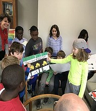 Ellen Hoitsma with her third grade students presenting their posters to Dan Paradis, head of school.