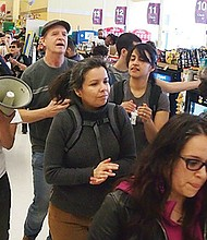 Members of Movimiento Cosecha danced in a Jackson Square, Jamaica Plain Stop & Shop as part of a demonstration raising attention to the movement's plans for a May 1 general strike.