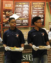 "To help teach players the value of work, Tri-State Ballers ""work"" as guest servers at a local McAlister's Deli in Southaven. Any tips they receive help finance the team. Here, Tylan Shaw (left) and Damien Jordan prepare to deliver meals to waiting guests."