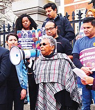 Dorotea Manuela of the Boston May Day Coalition, an alliance of immigrant rights groups, spoke during a rally on the State House Steps, flanked by Sen. Jamie Eldridge (left) and Roxana Rivera, 32BJ SEIU vice president. The coalition has scheduled marches on May 1 to promote legislation to protect immigrants and other workers.