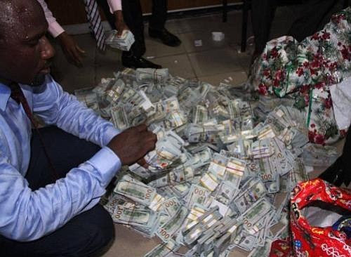 Neatly bound bundles of fresh U.S. dollars, Nigerian naira and British pounds totaling more than $50 million were recovered by ...