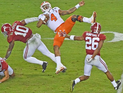 Alabama linebacker Reuben Foster (10) lays a big hit on Clemson quarterback Deshaun Watson during the National Championship game as cornerback Marlon Humphrey (26) looks on.